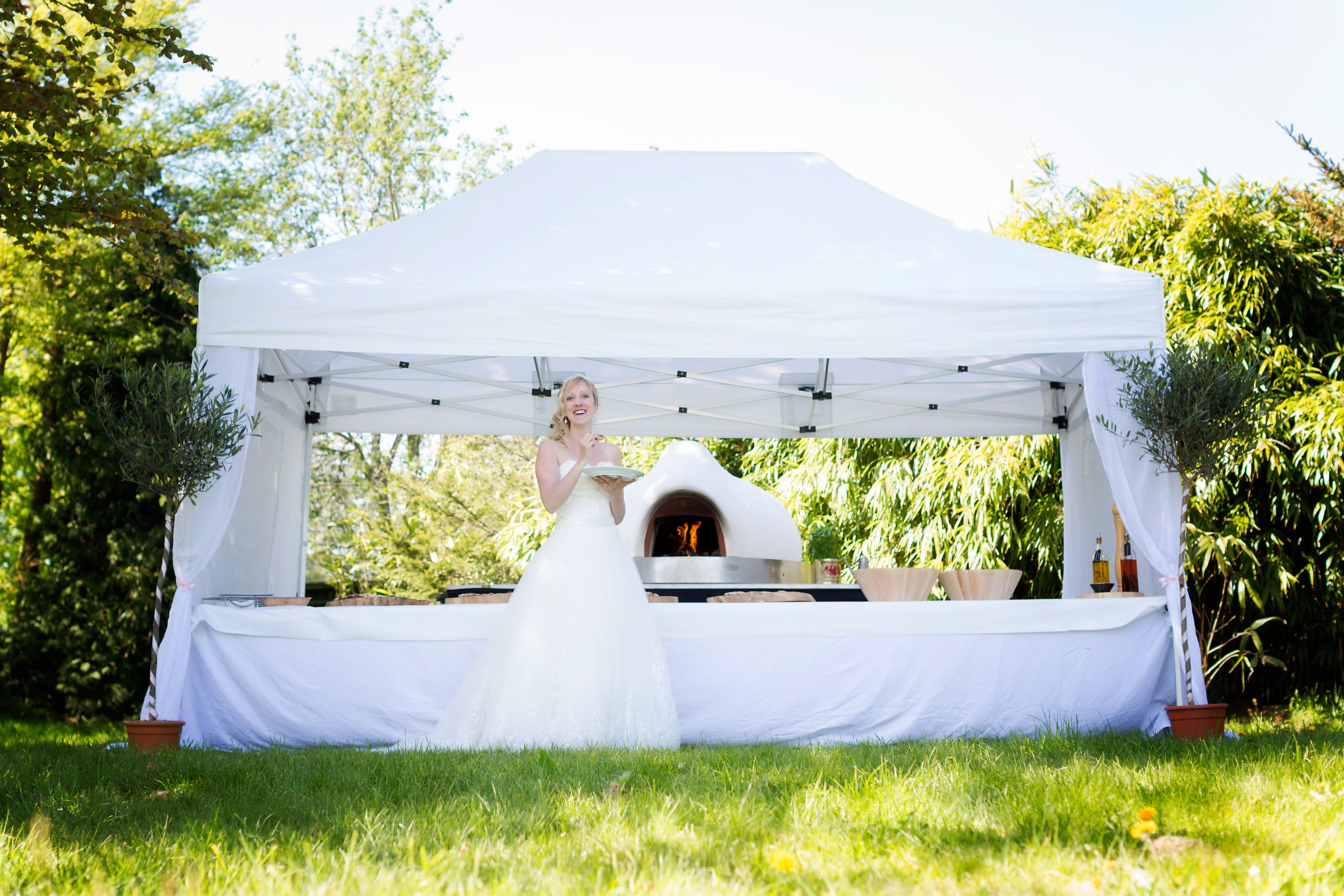 bride eating fresh pizza at her outdoor wedding